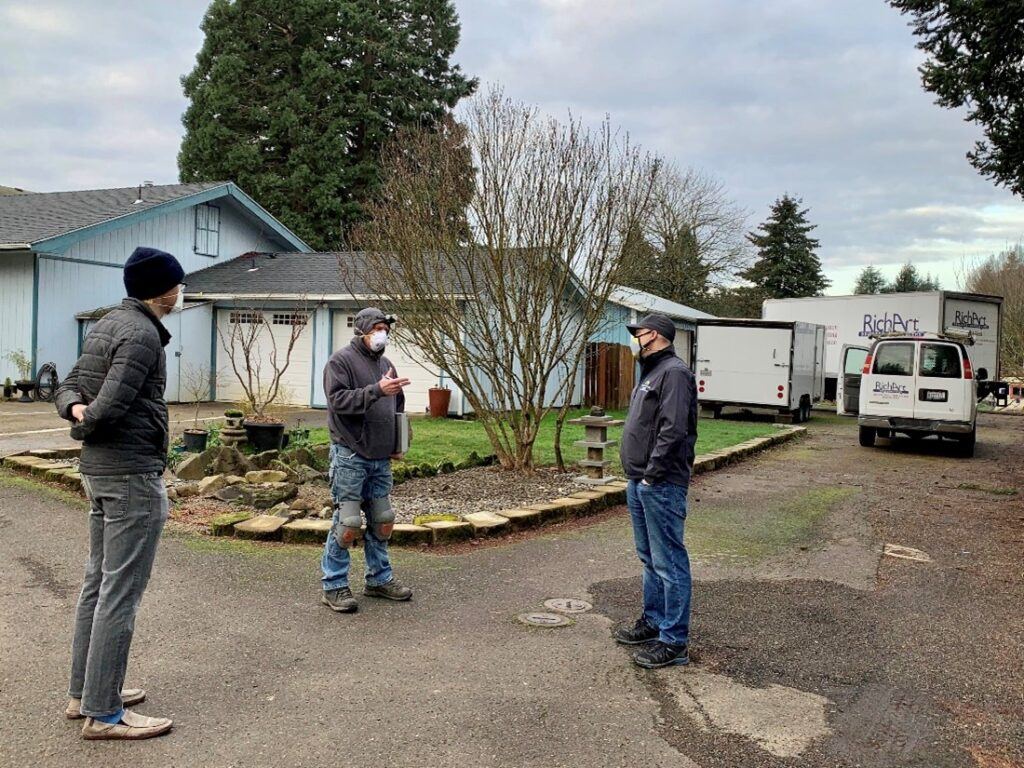Three contractors stand six-feet apart facing each other in front of a residential home.