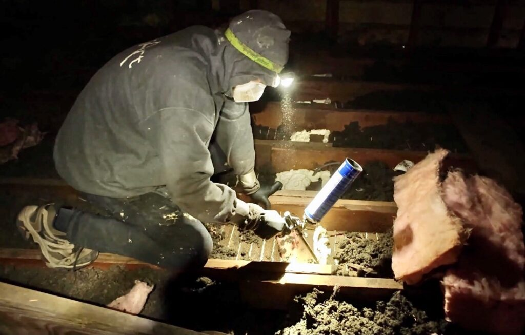 A contractor with headlamp and facemask is air sealing open parts of an attic before installing insulation.