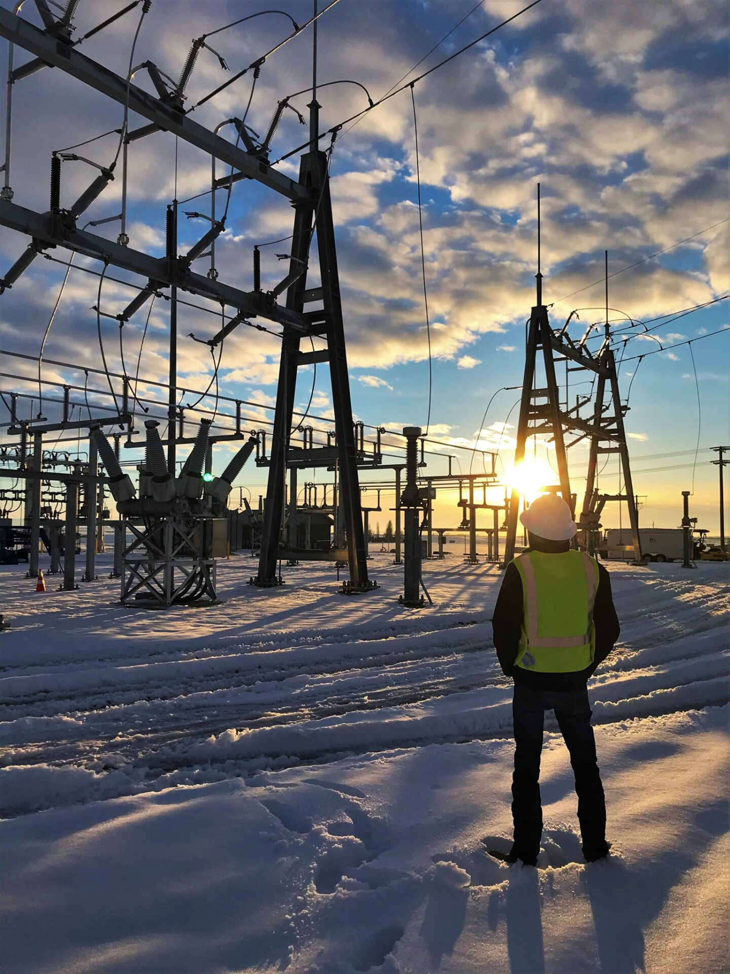 worker standing in snow looking at power lines